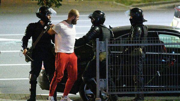 Сотрудники правоохранительных органов и участник акции протеста в Минске