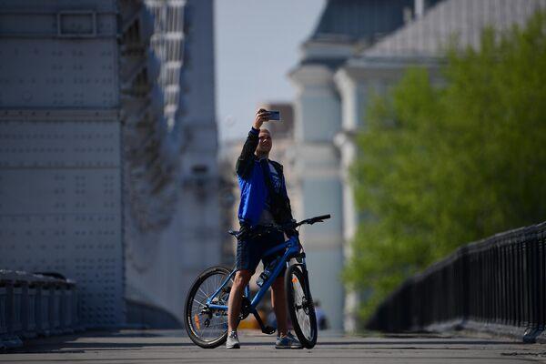 Велосипедист фотографируется на Крымском мосту