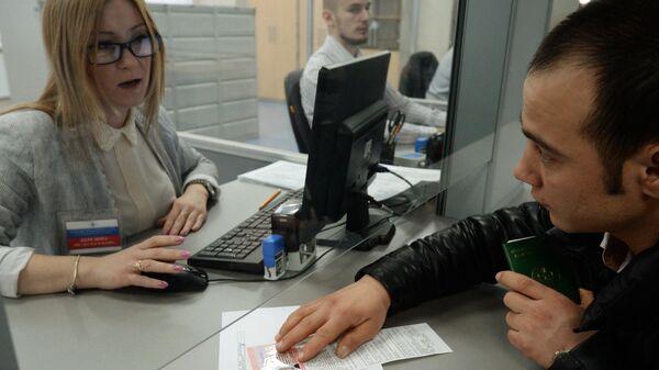 Иностранный гражданин разговаривает с сотрудником центра, получая трудовой патент