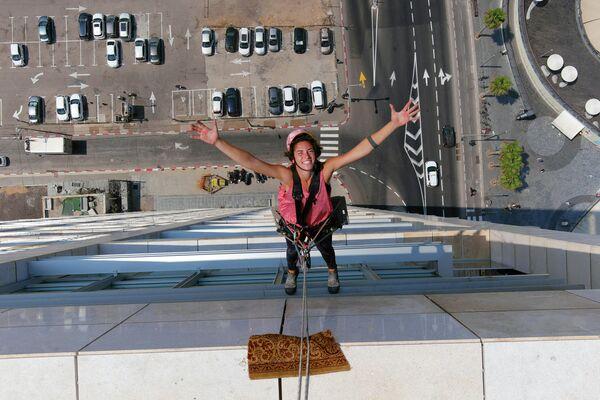 Мойщица окон Ноа Толедо позирует у фасада высотного здания в Тель-Авиве