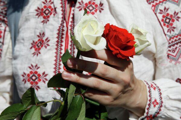 Женщина держит розы во время митинга в поддержку белорусской оппозиции в центре Киева