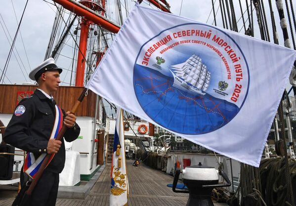 Курсант с флагом экспедиции на борту барка Седов перед отправлением по Северному морскому пути из Владивостока в Калининград