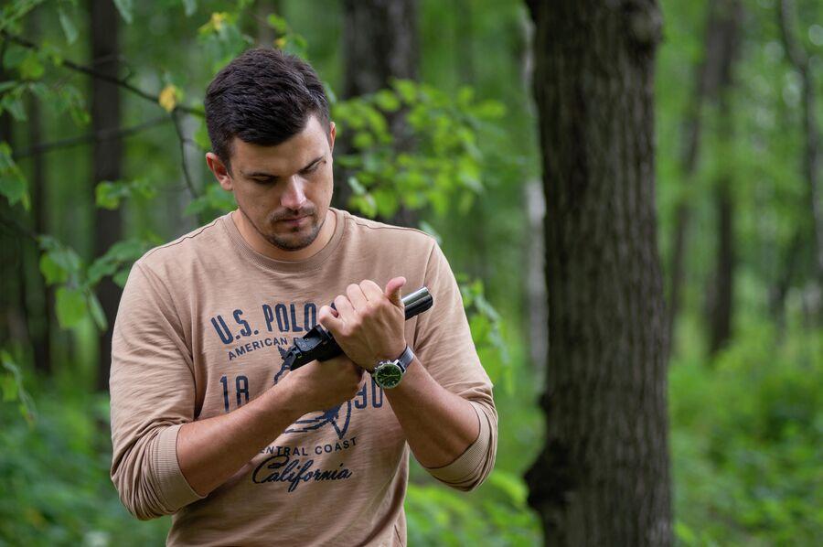 Корреспондент РИА Новости Андрей Станавов осматривает спортивный пистолет Аспид
