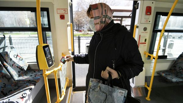 Женщина прикладывает социальную карту к валидатору в салоне городского автобуса