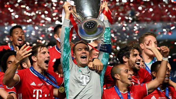 Вратарь Баварии Мануэль Нойер с трофеем Лиги чемпионов и партнерами по команде