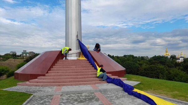 Сотрудники коммунальных служб снимают самый большой флаг Украины в Киеве