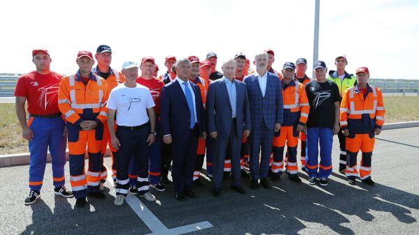 Президент РФ Владимир Путин с рабочими, которые принимали участие в строительстве, на церемонии запуска движения по трассе Таврида в Крыму