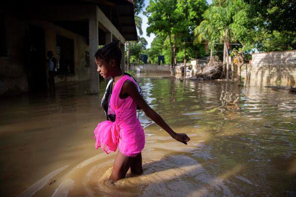 Девушка идет по затопленной улице после урагана Лаура в Порт-о-Пренсе, Гаити