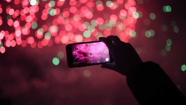 Девушка снимает на смартфон мультимедийное световое шоу в рамках международного фестиваля Круг света