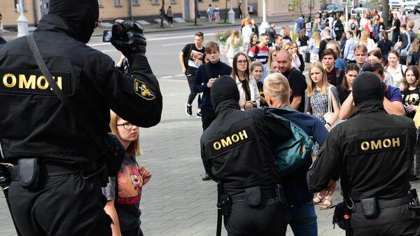Сотрудники ОМОНа во время задержания участника акции в Минске