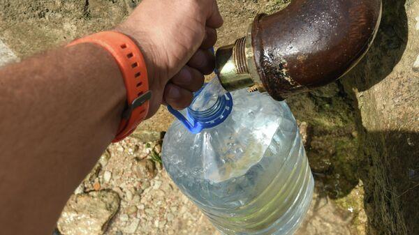 Мужчина набирает воду из родника в селе Дружное Симферопольского района