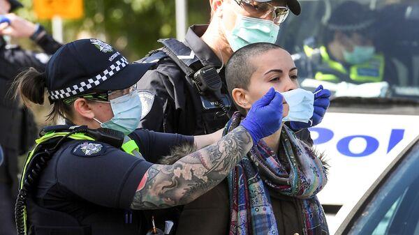 Полицейский надевает маску на задержанного во время демонстрации против карантинных мер, связанных с коронавирусом в Мельбурне, Австралия