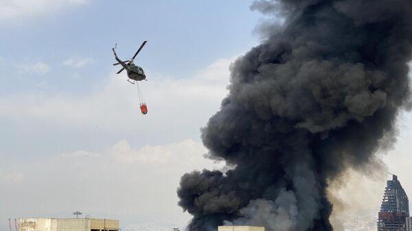 Вертолет во время тушения пожара на территории порта в Бейруте