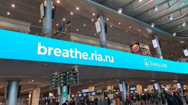 Трансляция ролика акции Пожалуйста, дышите! на медиафасаде атриума аэропорта Домодедово