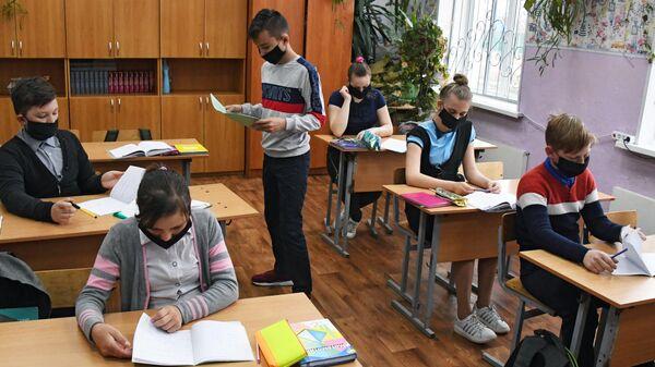 Ученики в защитных масках на уроке в общеобразовательной школе
