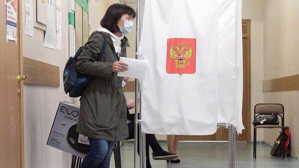 Девушка голосует на избирательном участке во время выборов губернатора Ленинградской области