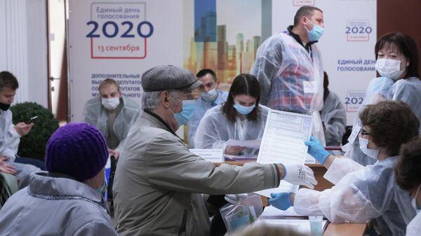 Избиратели и члены избирательной комиссии на избирательном участке No524 в Москве