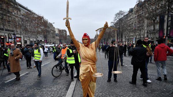 Женщина в костюме богини правосудия на протестной акции