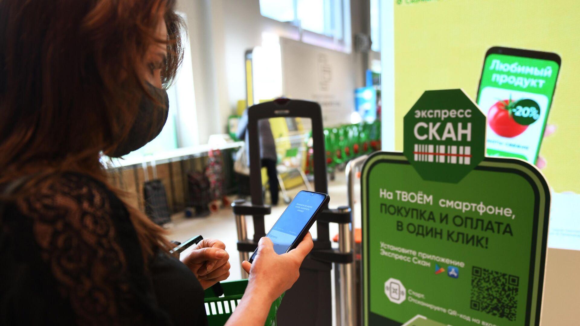 Девушка устанавливает мобильное приложение на смартфон, с помощью которого можно совершать бесконтактную оплату покупок - РИА Новости, 1920, 23.10.2020