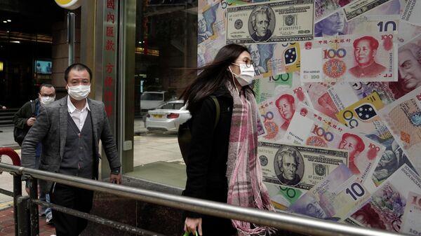 Люди в защитных масках проходят мимо пункта обмена валют в Гонконге