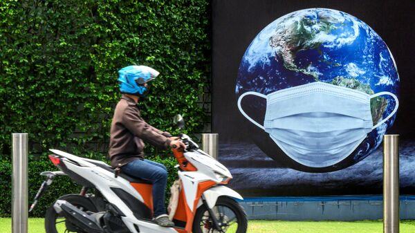 Мужчина на скутере у плаката в Бангкоке