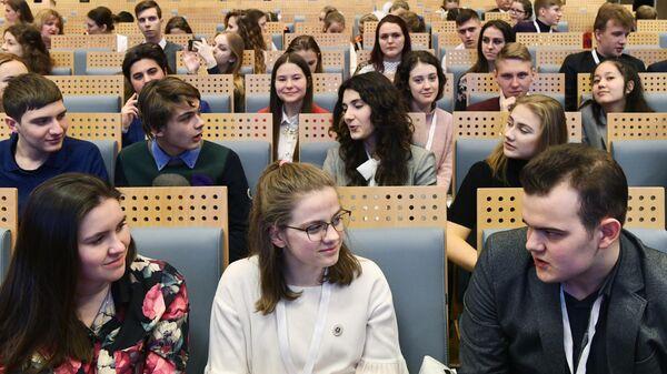 Молодые люди в зрительном зале во время конференции