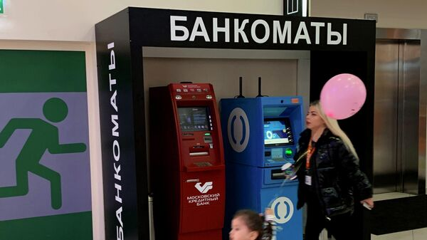 Женщина с ребенком проходят мимо банкоматов