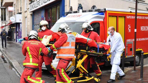 Французские пожарные несут раненого возле бывшего офиса французского сатирического журнала Charlie Hebdo в Париже