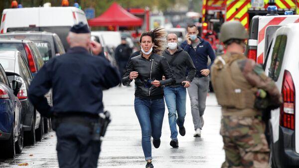 Прохожие на месте нападения у бывшего офиса французского сатирического журнала Charlie Hebdo в Париже