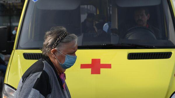 Пожилая женщина в медицинской маске у автомобиля скорой помощи на улице в Москве