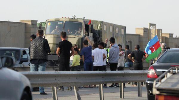 Люди приветствуют военнослужащих армии Азербайджана по дороге в Баку, 27 сентября 2020 года