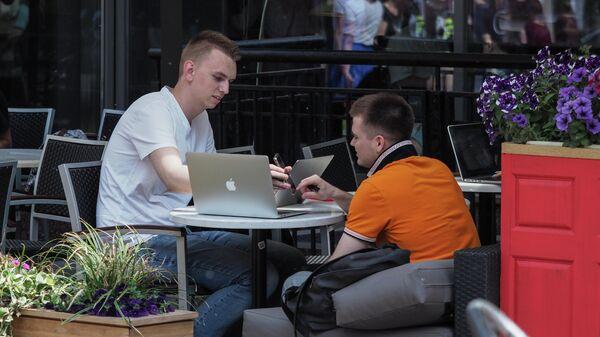 Посетители на летней веранде кафе на улице Арбат в Москве