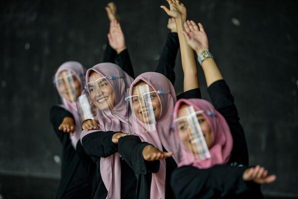 Девушки танцуют в защитных масках для лица во время тренировки в художественном и культурном центре в Банда-Ачехе, Индонезия