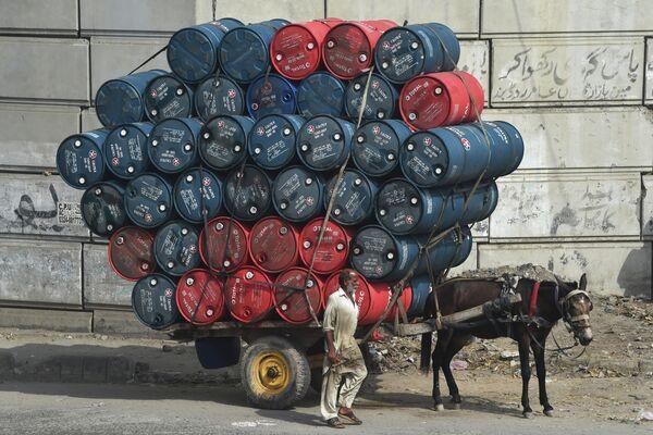 Мужчина рядом с повозкой груженной бочками с нефтью на  улице в Лахоре