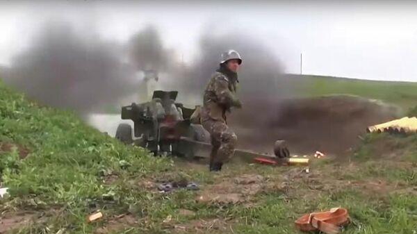 Военнослужащий стреляет из пушки по позициям вооруженных сил Азербайджана на линии соприкосновения в Нагорном Карабахе. Стоп-кадр видео