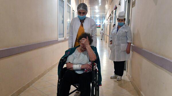 Сотрудница госпиталя перевозит женщину, пострадавшую в результате обстрела города Гянджа