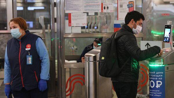 Молодой человек у турникета с установленным дистанционным тепловизором на станции метро Спартак в Москве