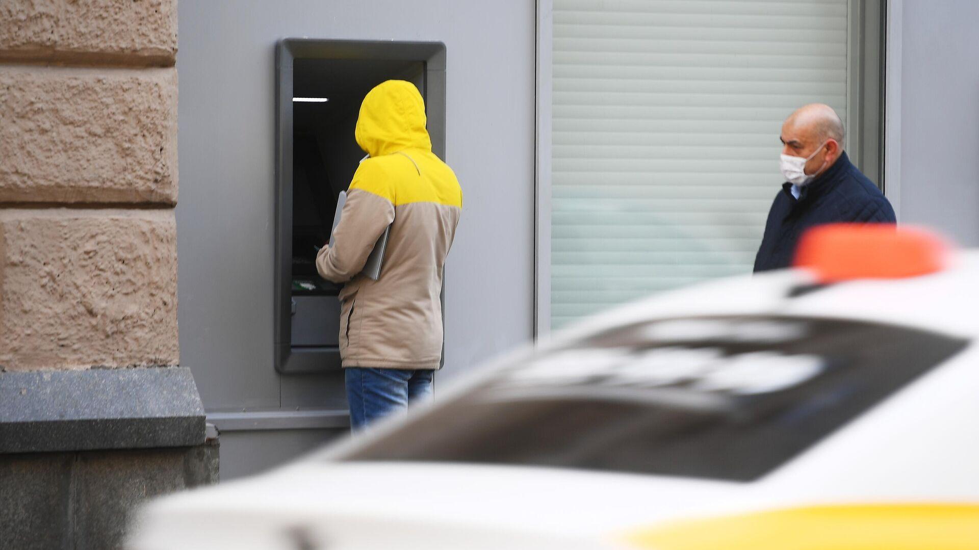 Мужчина у банкомата и прохожий в защитной маске - РИА Новости, 1920, 31.03.2021