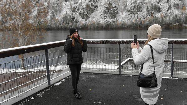 Девушки фотографируются после первого снегопада на набережной Енисея в городе Дивногорске Красноярского края