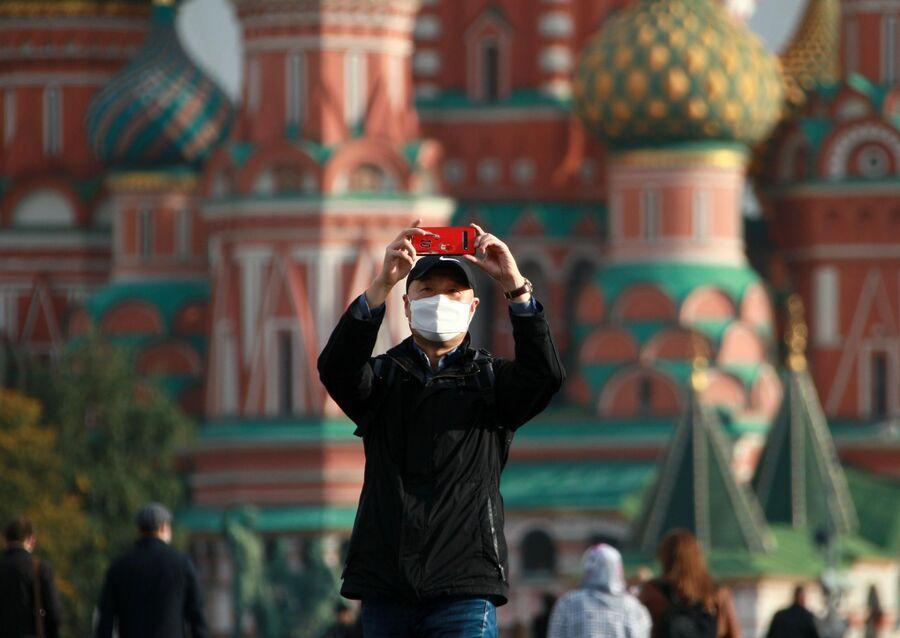 Мужчина в медицинской маске фотографируется около Собора Василия Блаженного на Красной площади в Москве
