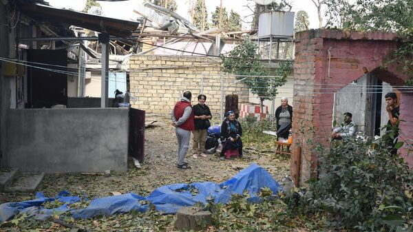 Местные жители домов, пострадавших в результате ракетного обстрела города Гянджа