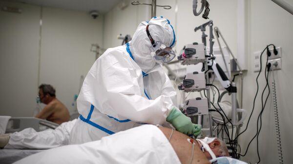 Медицинский работник и пациенты во временном госпитале для пациентов с COVID-19 в ледовом дворце Крылатское в Москве