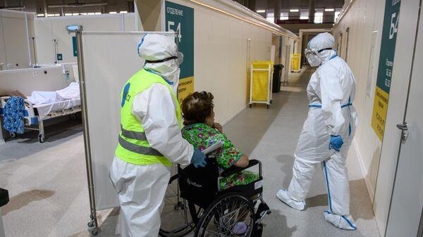 Медицинские работники и пациент во временном госпитале для пациентов с COVID-19 в ледовом дворце Крылатское в Москве