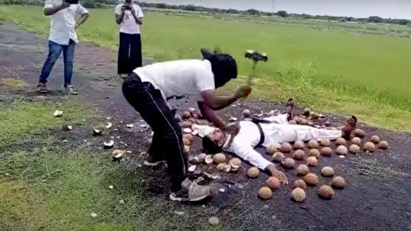 Стоп-кадр видео установления мирового рекорда по разбиванию кокосов кувалдой с завязанными глазами
