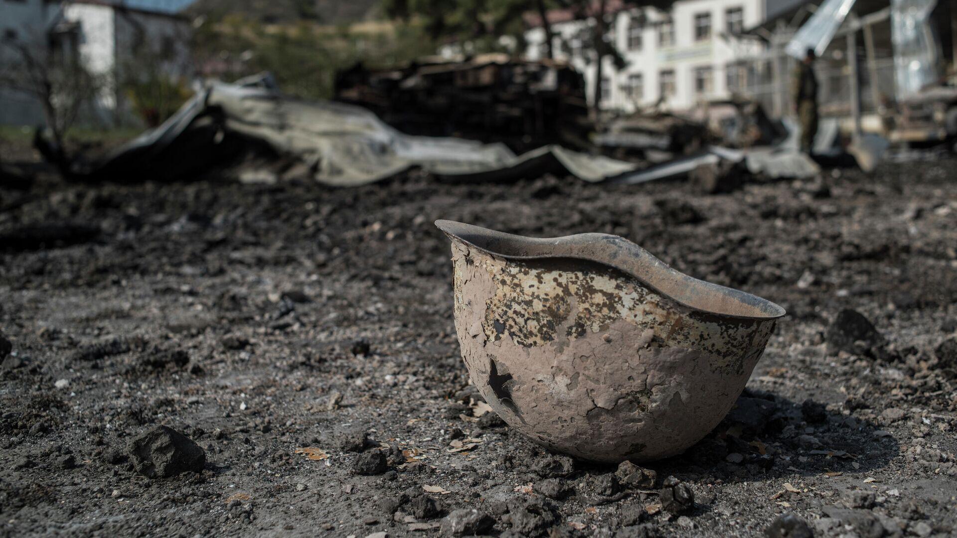 Пробитая каска на территории у госпиталя в Мартакерте, разрушенного в результате обстрела - РИА Новости, 1920, 18.12.2020