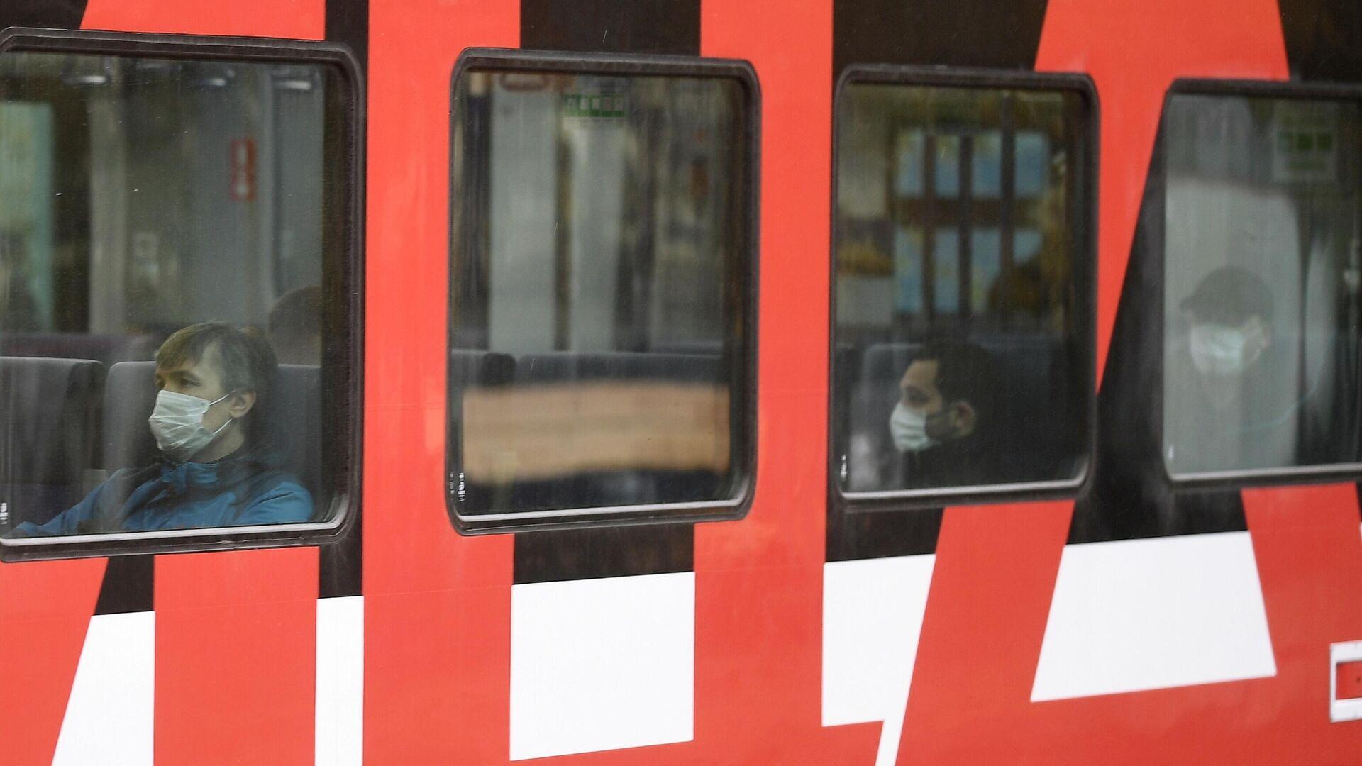 Пассажиры в медицинских масках в вагоне электрички  - РИА Новости, 1920, 27.10.2020