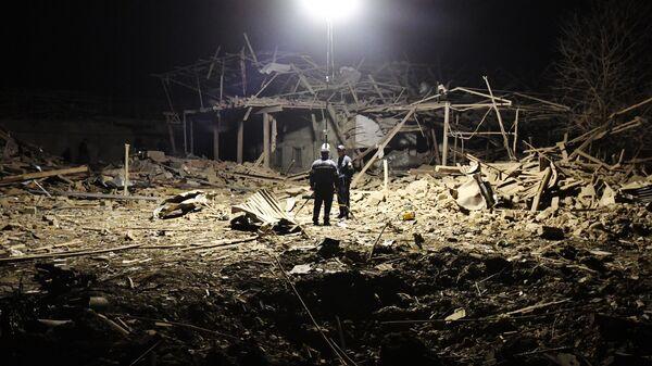 Сотрудники МЧС Азербайджана дежурят на месте разбора завалов разрушенных домов после ракетного обстрела города Гянджа