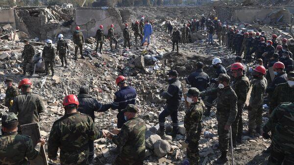 Сотрудники МЧС Азербайджана на месте разбора завалов разрушенных домов после ракетного обстрела города Гянджа