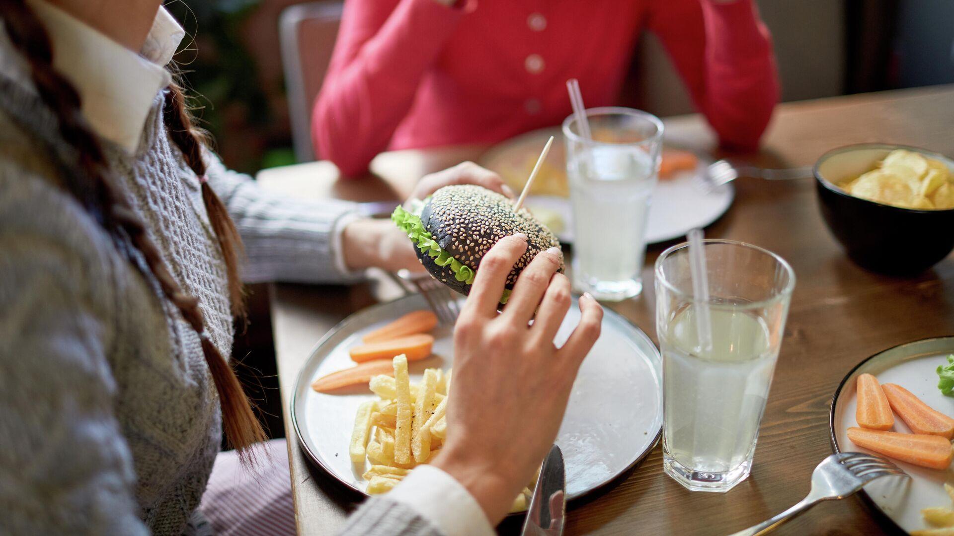 Девушки едят чизбургеры и картофель в кафе  - РИА Новости, 1920, 22.10.2020