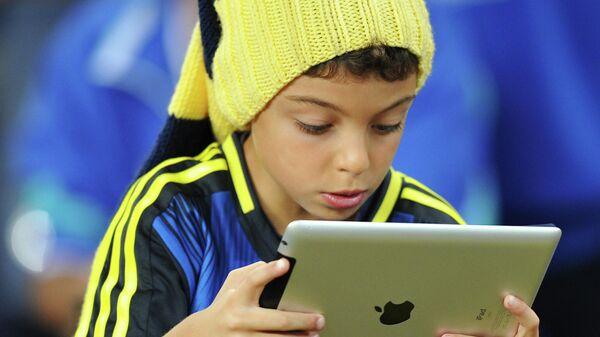Ребенок с планшетом в руках во время футбольного матча